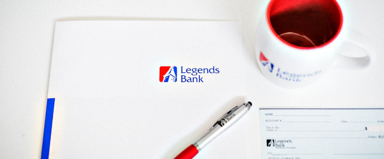 A photo of a desk with a Legends Bank folder, pen, check, and cup.