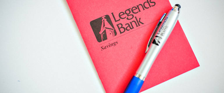 A photo of a Legends Bank Savings booklet and pen.