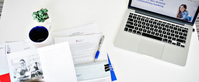A photo of an above view of a workspace with Legend's Bank papers and checks next to a laptop with the Legends Bank website on screen.