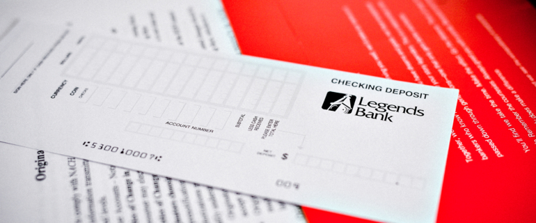 A photo of a close-up of a Legends Bank Checking Deposit slip.