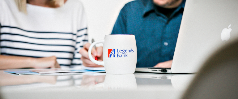 A photo of a Legends Bank coffee cup. In the background is two people discussing paperwork.