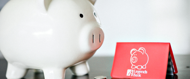 A photo of a piggy bank with coins next to a Legends Bank savings booklet.