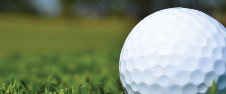 A photo of a close-up of a golf ball in grass.
